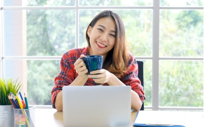 Girl Drinking Coffee In Front Of A Computer